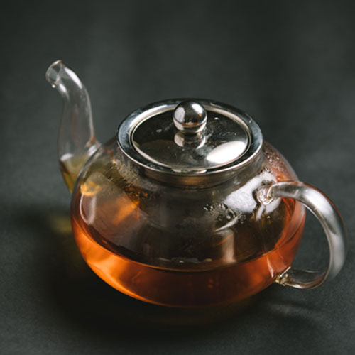 A glass kettle filled with hot tea, placed on a dark surface