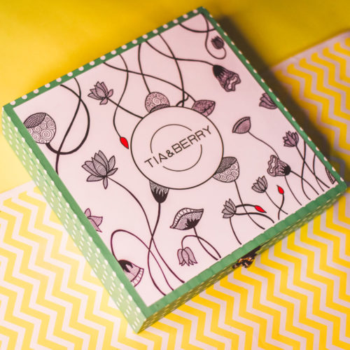 A square box containing sachets of Tia & Berry Tea Bags placed on a yellow and white surface .
