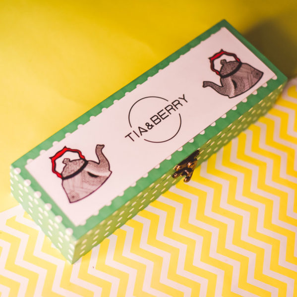 A beautiful rectangular box containing sachets of Tia & Berry Tea Bags placed on a yellow and white surface.