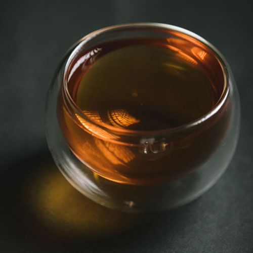 Double walled glass filled with tea, placed on a dark surface